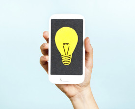 Hand showing a phone concept with a bulb on blue background
